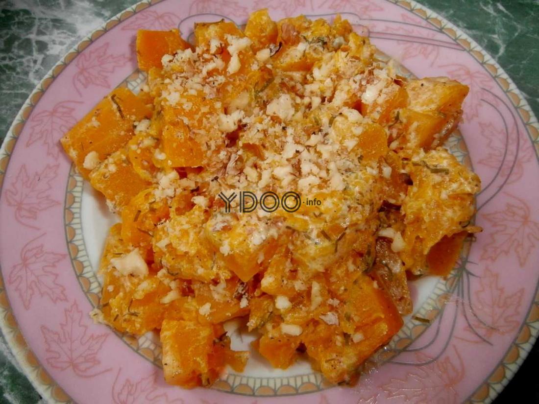 тушеная тыква, нарезанная квадратиками и присыпанная измельченными грецкими орехами, на тарелке с розовой каемкой