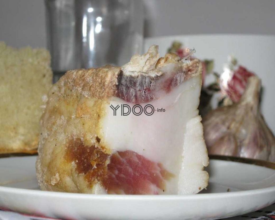 кусок вяленого сала в блюдце на столе, на фоне головка чеснока и кусочек хлеба