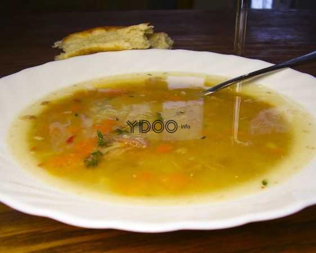 суп из тушенки в тарелке с ложкой внутри, на фоне кусок хлеба