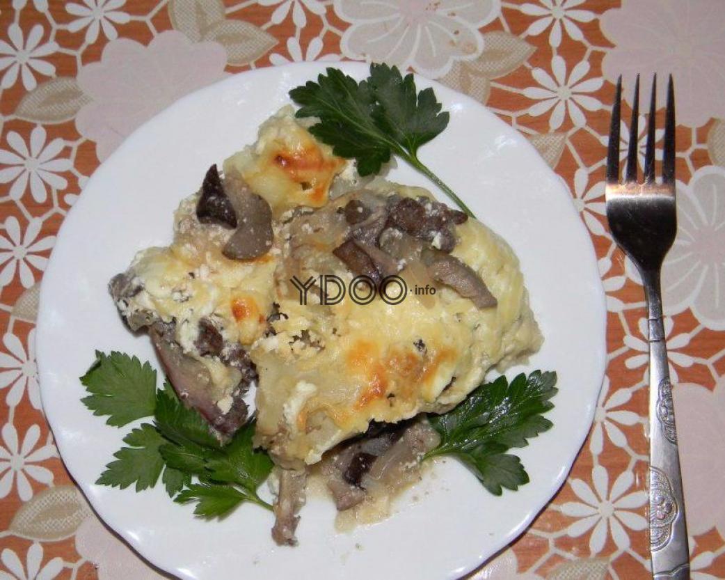 мясо зайца с грибами и картошкой под сырной корочкой с листиками свежей петрушки в тарелке, вилка рядом с тарелкой на столе